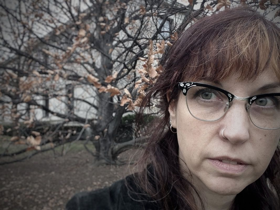 self portrait by Victoria Cable face close right side,left side large distant beech treePicture